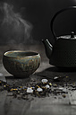 Japanese tea pot and bowl with tea leaves on wooden table, studio shot - SBD000157
