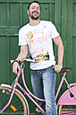 Germany, Bavaria, Portrait of mature man holding pink bicycle, smiling - MAEF006528