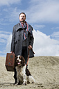 Germany, Bavaria, Mature man with dog standing in sand - MAE006553
