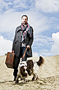 Germany, Bavaria, Man with dog standing in sand - MAE006552