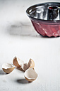 Eggshells and red cake tin, close up - SBDF000063