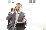 Germany, Businessman talking on mobile phone - MAEF006614