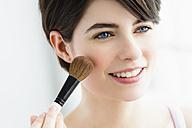 Germany, Bavaria, Munich, Young woman using blusher brush, close up - SPOF000408