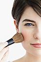 Germany, Bavaria, Munich, Young woman using blusher brush, close up - SPOF000410