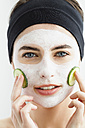 Germany, Bavaria, Munich, Portrait of young woman with cucumber mask, close up - SPOF000415