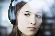 Germany, Cologne, Portrait of teenage girl listening music with headphones, close up - JAT000007