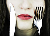 Teenage girl with knife and fork on face, close up - JAT000009