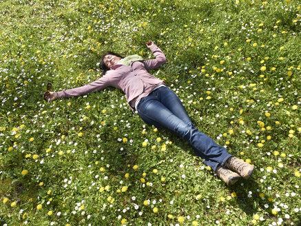 Germany, Hesse, Mature women lying on meadow - BSCF000276