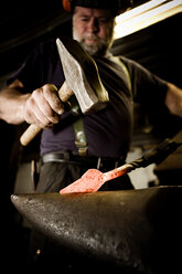 Blacksmith working with hammer at anvil - CNF000049