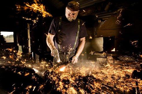 Blacksmith working with hammer at anvil surrounded by sparks - CNF000083