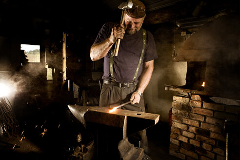 Blacksmith working with hammer at anvil - CNF000064