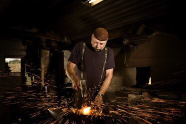 Blacksmith working with hammer at anvil surrounded by sparks - CNF000069