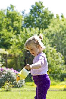 Germany, Kiel, Girl watering plants - JFEF000110