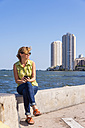 USA, Florida, Miami, Mature woman sitting on surrounding wall of port and holding smartphone - ABAF000844