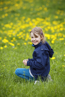 Germany, Baden Wuerttemberg, Portrait of girl sitting in meadow, smiling - SLF000134