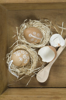 Painted eggs with eggshell in box, wooden spoon, close up - ASF004958