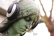 Germany, Cologne, Angel statue with headphones in cemetery - JAT000061