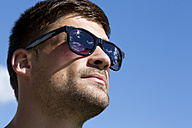 Germany, Bavaria, Portrait of young man wearing sunglasses and looking away - MAEF006687