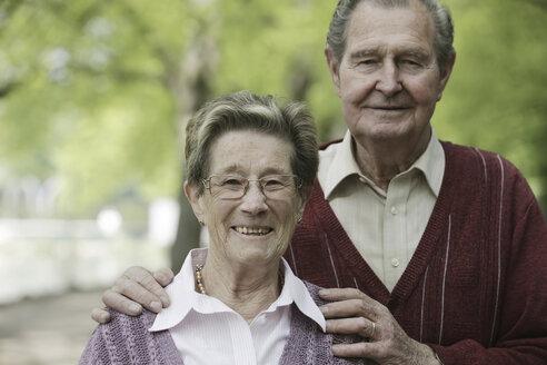 Germany, Cologne, Portrait of senior couple in park, smiling - JAT000063