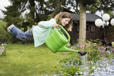 Germany, Bavaria, Kaufbeuren, Mid adult woman watering plants in garden - CAF000013