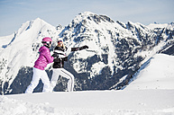 Austria, Salzburg, Young women walking in snow, smiling - HH004610