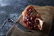 Knuckle of pork with knife on chopping board, close up - CSF019324