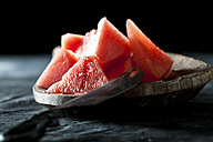 Slices of watermelon with knife on wooden spoon,close up - CSF019336