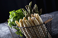 Bunch of green and white asparagus with herbs in wire basket, close up - CSF019386