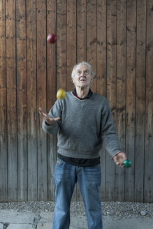 Senior man juggling with three balls - FB000354