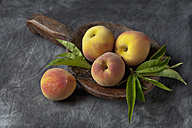 Peaches and leaves on wooden spoon, close up - CSF019361