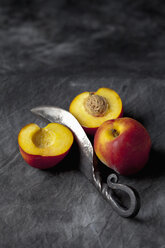 Peaches with knife on black textile, close up - CSF019354