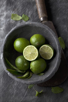Bowl of lime with sickle on black textile, close up - CSF019345