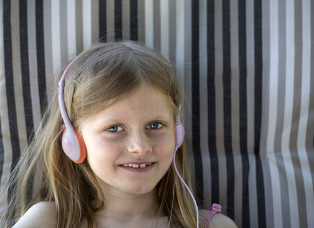 Austria, Girl with headphones sitting on gardenchair, smiling - CW000057