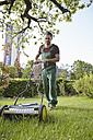 Germany, Cologne, Young man mowing lawn with push mower - RHYF000433