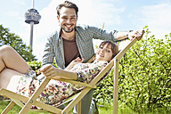 Germany, Cologne, Young couple relaxing in garden, smiling - RHYF000422