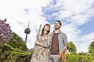 Germany, Cologne, Young couple holding bunch of carrots, smiling - RHYF000409
