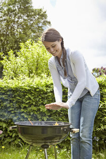 Germany, Cologne, Young woman warming hands in barbecue grill, smiling - RHYF000389