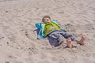 Germany, Mecklenburg Western Pomerania, Boy relaxing on sand at baltic sea - MJF000190