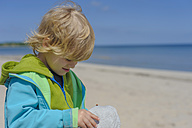 Germany, Mecklenburg Western Pomerania, Boy looking at cap at beach - MJF000169