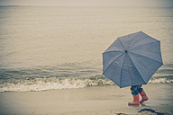 Germany, Mecklenburg Western Pomerania, Boy with umbrella in rain at baltic sea - MJ000207