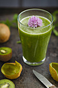 Glass of smoothie with kiwi, parsley and blooming chives, close up - ECF000186