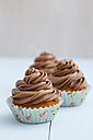 Cupcakes topped with chocolate buttercream on wooden table, close up - ECF000177