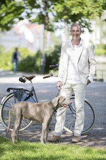 Germany, Bavaria, Portrait of mature man with Weimaraner dog, smiling - MAEF006831