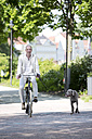 Germany, Bavaria, Portrait of mature man riding bicycle with Weimaraner dog, smiling - MAEF006832