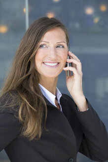 Germany, Berlin, Businesswoman talking on smart phone, smiling - FKIF000012