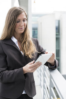 Germany, Berlin, Businesswoman using digital tablet, smiling - FKIF000018