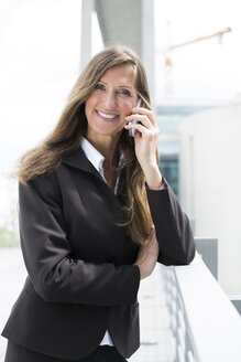 Germany, Berlin, Portrait of businesswoman talking on smart phone, smiling - FKIF000021