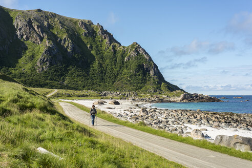 Norway, Mature woman hiking at coastline - HWO000018