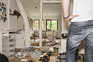 Germany, North Rhine Westphalia, Mature man looking at messy home - ONF000206