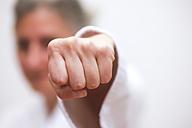 Germany, Saxony, Mature woman doing martial arts, close up - JT000421
